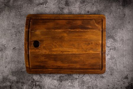 Photo for Top view of wooden cutting board on old stone countertop. - Royalty Free Image