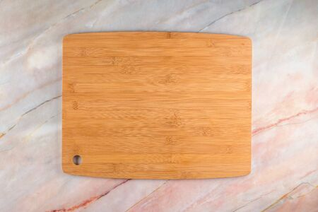 Photo pour Top view of wooden cutting board on a gray marble background with space for text. - image libre de droit