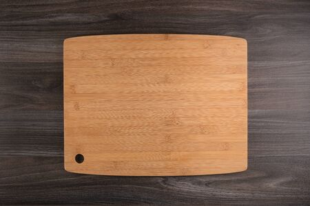 Photo for Top view of wooden cutting board on old dark wood countertop. - Royalty Free Image