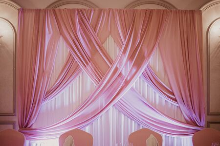 Photo pour Wedding pink decoration in the restaurant. Pink fabric wall over the table of wedding couple. - image libre de droit