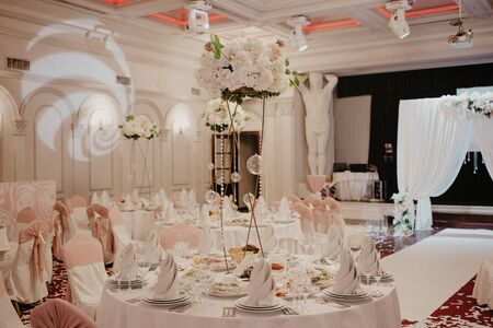 Photo pour Wedding flowers decoration in the restaurant. Banquet round tables, decorated with a bouquet of white flowers in the center of the tables. - image libre de droit