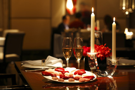 Photo pour Romantic table setting with Chocolates, Candle and Wine - image libre de droit