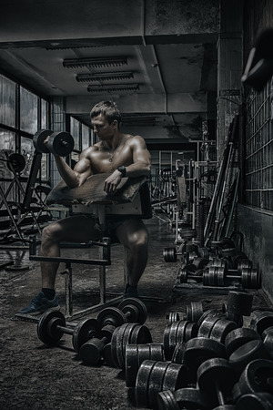 Photo pour Young handsome athlete in old rusty gym - image libre de droit