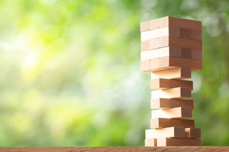 Photo pour Wooden stack tower from wood blocks toy on greenery blurred background with copy space. Business strategy, construction, leaning, and development concept - image libre de droit