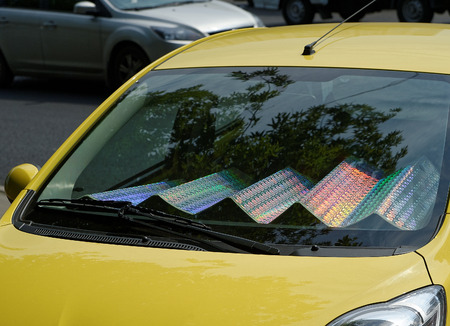 The car with sun shade on the windshield in a parking lot. Folding holographic Sunshade.