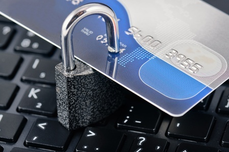 Credit card with the padlock on a background laptop. Symbolizes reliability and safety of the Internet