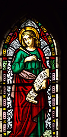 detail of viktorian stained glass church window in Fringford depicting St John the Evangelist, a scroll in his hands with the beginning of his gospel in latin In principio erat verbum