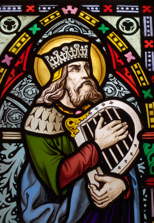 detail of victorian stained glass church window in Fringford depicting King David, the author fo the psalms in the Old testament with a hand harp