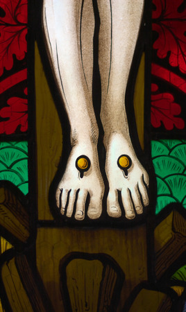 detail of victorian stained glass church window in Fringford depicting Jesus' feet nailed to the cross
