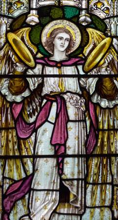detail of victorian stained glass church window in Fringford depicting a typical victorian angel with cymbals in his hands