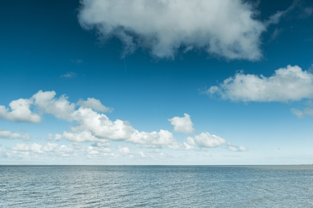 Nautical background of a calm blue ocean on the North Sea Coast, Germany on a sunny day with fluffy white clouds in a blue sky in a panoramic view