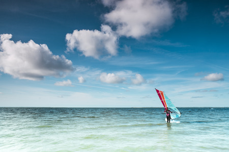 Wind surfer on his board on a calm ocean at the North Sea on a sunny blue sky day with clouds in a marine or nautical travel themed concept or healthy outdoor lifestyle