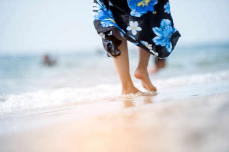 Photo for Woman bare foot walking on summer beach. close up leg of young woman walking along wave of sea water and sand on vacation beach. Enjoyment barefoot walk outdoor with freedom. Relaxation Travel Concept. - Royalty Free Image