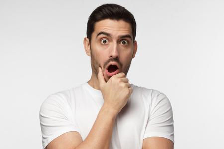 Horizontal portrait of young European man isolated on grey background pictured with eyes wide open with fear or amazement, covering open mouth with palm, astounded with news