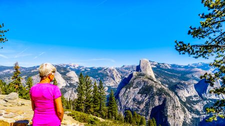 Photo pour Senior Woman enjoying the view from Glacier Point at the end of Glacier Point Road of the Sierra Nevada high country, with the curved tooth of the famous Half Dome in the foreground in Yosemite National Park, California, USA - image libre de droit