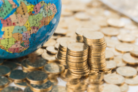 Photo for Stacked gold coins and globes background - Royalty Free Image
