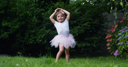Photo pour On a sunny spring day a baby girl dressed as a dancer plays tries to stand up and take her first steps alone without a mother - image libre de droit