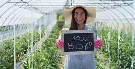A beautiful girl in a straw hat and in pink gloves, holds a shovel for planting, in a greenhouse. Concept: bio products, natural products, fresh, delicious, fruits, vegetables, grow water plants