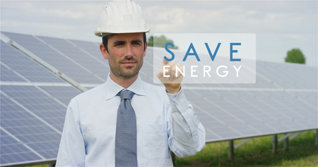 """Foto de A futuristic technical expert in solar photovoltaic panels, selects the """"Green solution"""" function using pure renewable energy. The concept of remote support technology, ecology and remote control - Imagen libre de derechos"""
