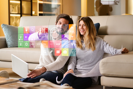 Foto de A couple sitting on the sofa controls all the functions of the house such as wi-fi, heating, lighting, and television through holography. Concept of, home automation, automations, future, technology. - Imagen libre de derechos