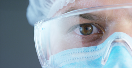 Photo for A doctor or surgeon in a medical mask, a respirator, brown eyes, goggles, a surgical cap, a hospital or clinic. - Royalty Free Image