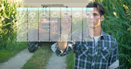 Foto de Futuristic young farmer (student) working in the field, tractor, hologram controls the weather, happy, in shirt, cornfield - Imagen libre de derechos