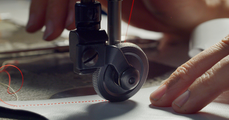 Photo pour Close up of a shoemaker sewing with red leather Concept: handmade, fashion, industrial, factory. - image libre de droit