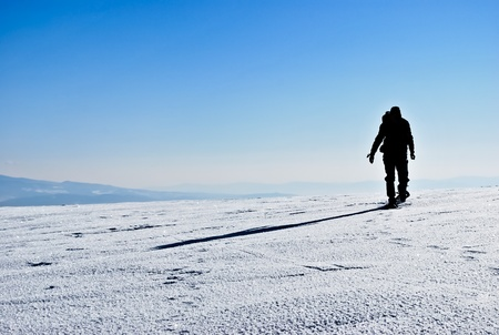 Silhouette and shadow of hiker running on snowy mountain ridge