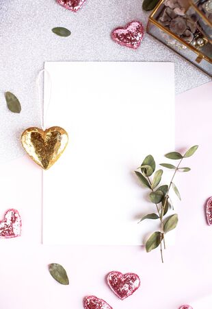 Photo pour Background with copy space blank on table with glitter heart, eucalyptus branch, flowers and leafs. White paper top view, flat lay, minimal style. Moke up card - image libre de droit
