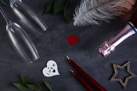 Photo pour Flat lay composition with bottle of champagne, candles, feather and hearts for celebration on grey concrete background. Glass for champagne - image libre de droit