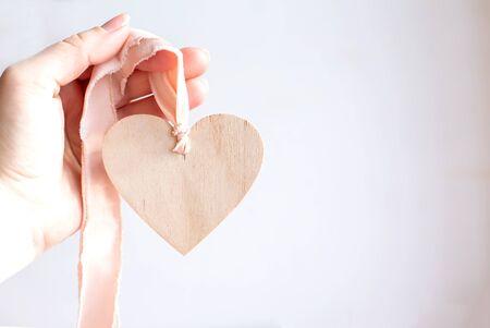 Foto de Light wooden heart on a silk pink ribbon. Hand holding a wooden heart pendant on a chiffon ribbon. Copy space. - Imagen libre de derechos
