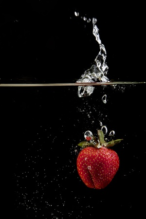 A single fresh strawberry is dropped into water on black backgroundの写真素材