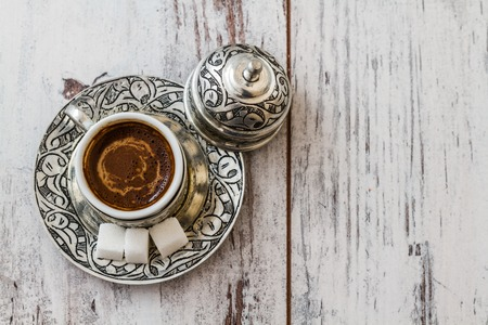 Traditional Turkish coffee in traditional silver cup on white wooden table