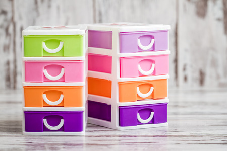 Photo for Small, cute and colorful plastic drawers on white wooden background - Royalty Free Image