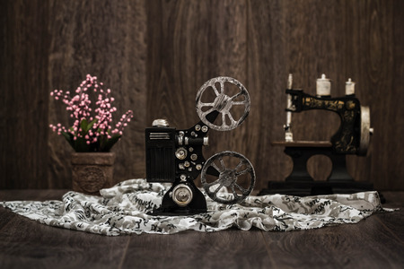 Small nostalgic decorative film camera on brown wooden background