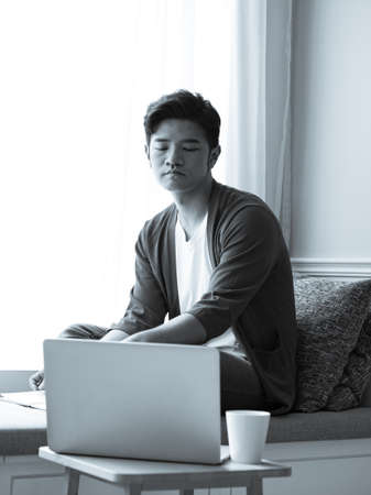 Photo pour Asian young man sitting at the table in front of laptop computer - image libre de droit