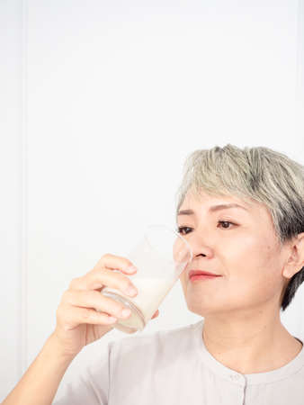 Foto per Portrait of a senior asian woman with a glass of milk. - Immagine Royalty Free