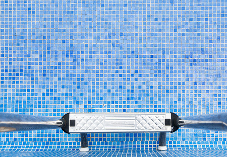 An empty swimming pool with blue tiles