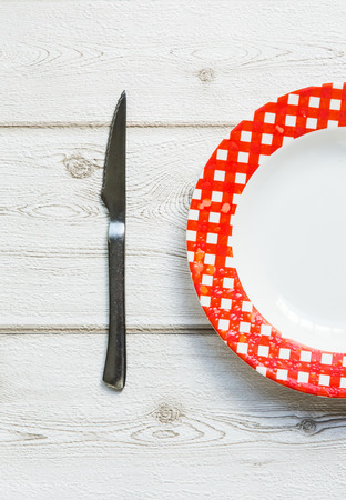 knife and fork and plate on old wooden background