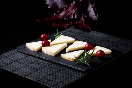 Foto de Typical Spanish cheese with wine, grapes and cherry tomatoes on old wooden table - Imagen libre de derechos