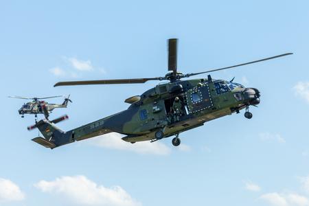 BERLIN / GERMANY - JUNE 28, 2018:  german military transport helicopter, NH 90 flies on airfield in Berlin, Germany.