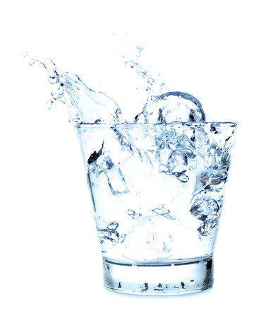Splashing of water with ice in glass on white background