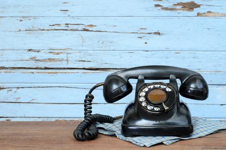 Old telephone on wood background.