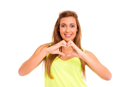 Beautiful teenager making a heart shape with her hands, isolated over white background