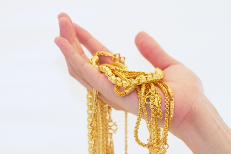 A hand holding gold necklaces