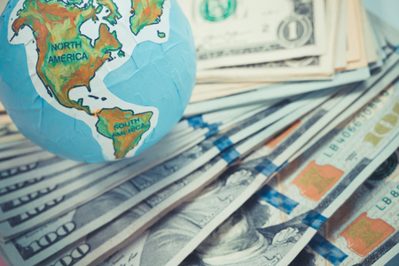 handmade globe on us dollar banknotes, business and finance concepts