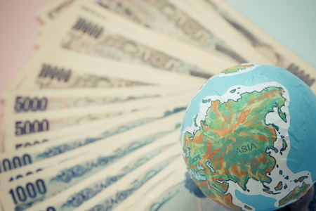 handmade globe on japanese banknotes, business and finance concepts