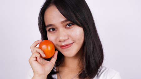 Photo for Close up beautiful asian women with a tomato isolated on white background - Royalty Free Image