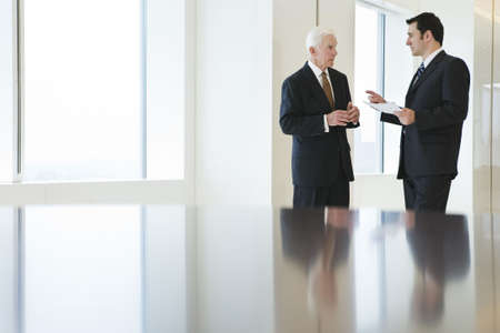 Two businessmen in focus in the background near bright windows of a conference room .