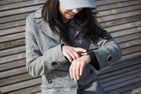 Young brunette girl in grey coat using her smart watch while sitting on the bench outdoors. This person is always connected to social media and internet everywhere.